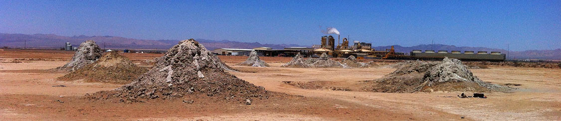 Photo of mud volcano, not eropting, with geothermal plant in background.