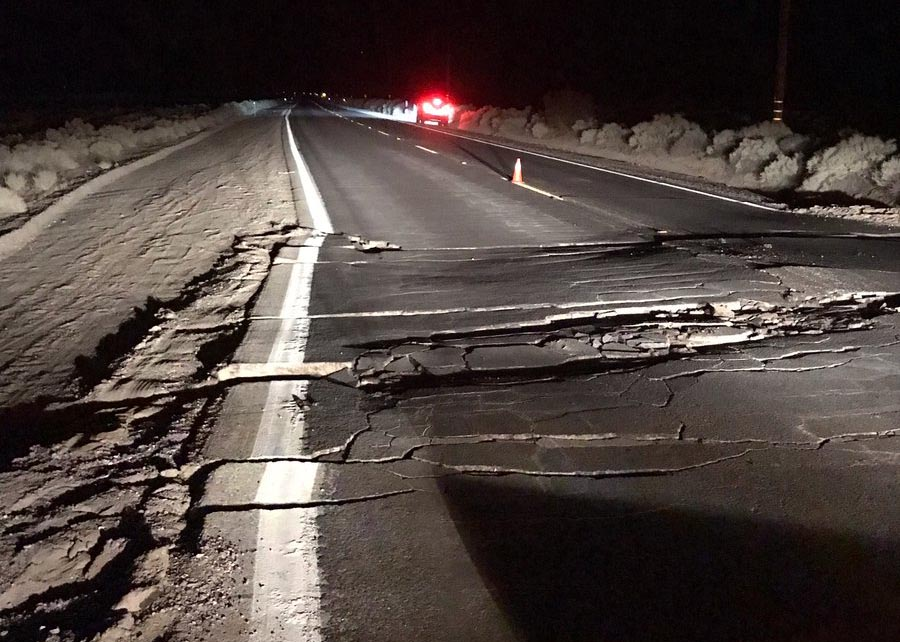 Photo showing line of damaged asphalt on darkened highway.