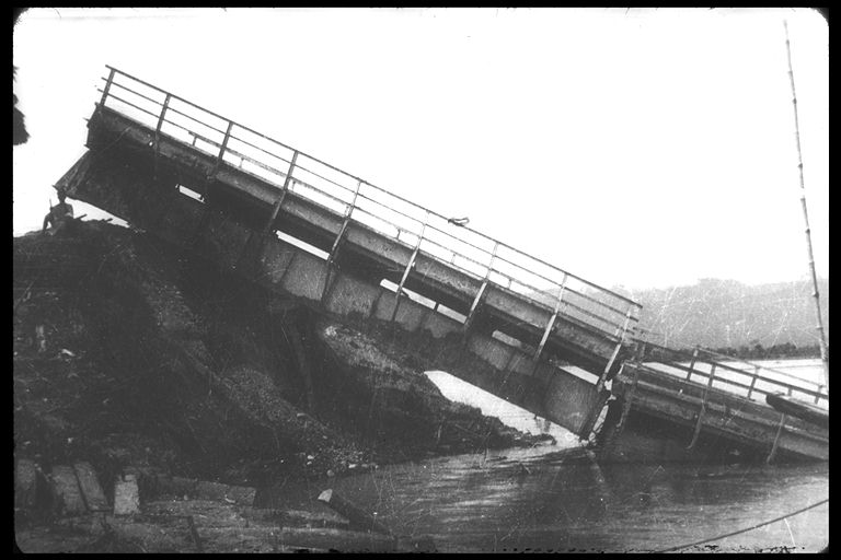 Black and white photo of fallen bridge sitting in water.