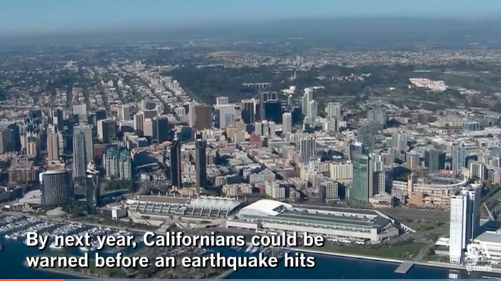 Ariel view of city with text: By next year, Californians could be warned before an earthquake hits
