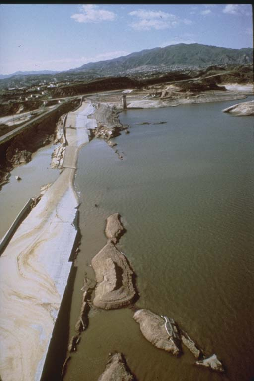 Old color photo of water nearly overtopping a crumbling dam.